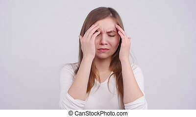 Woman with a headache holding head on a white background
