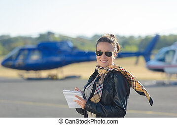 woman with a helicopter in the background