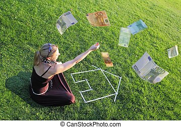 Woman with a house and money - Woman sitting on green grass...