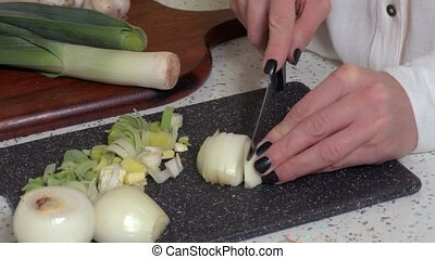 Woman with a knife cut onion in kitchen