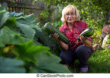 Woman with a large zucchini holding