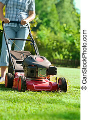 woman with a lawn mower in front of back yard