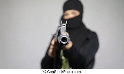 Woman with a machine gun. Muslim woman pointing a machine...