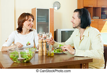 woman with a man eating a veggie salad at home