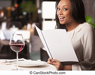 Woman with a Menu. Beautiful African descent women holding a...