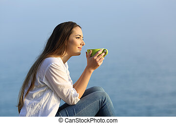 Woman with a mug relaxing at sunset on the beach