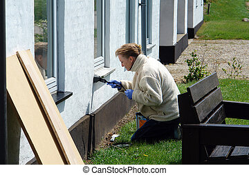 Woman with a paintbrush painting a house