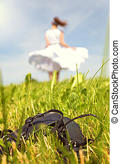 Woman with a petticoat dress dancing on the meadow, shoes in the front