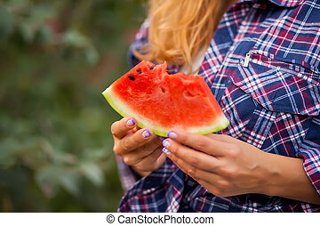 Woman with a piece of ripe watermelon in a hand in a picnic. Autumn harvest. Autumn concept