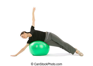 Woman with a Pilates Ball - Pretty fit woman training with a...