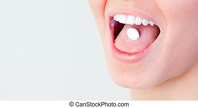 Woman with a pill in her mouth
