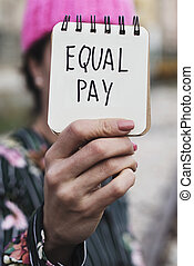 woman with a pink hat and the text equal pay - closeup of a...