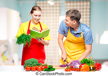 woman with a recipe book, a man cuts vegetables cooked together a salad in the kitchen