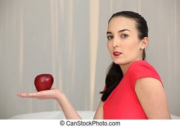 Woman with a red apple in the palm of her hand