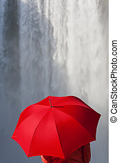 Woman With a Red Umbrella In Front Of A Waterfall