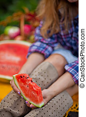 Woman with a ripe piece of watermelon in a hand on a autumn picnic. Autumn harvest. Autumn concept.