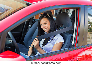 Woman with a seat belt in a car - Young woman strapped to ...
