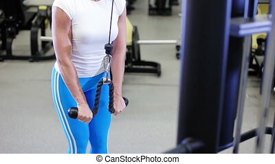 woman with a sexy body doing exercise in the gym