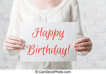 woman with a sign in her hands with the words happy birthday