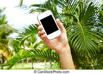 Woman with a smartphone in tropical garden.