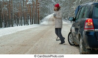 woman with a straw car on the road in winter