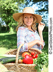 Woman with a straw hat and basket of vegetables.
