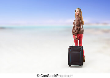 Woman with a suitcase on the beach