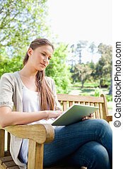 Woman with a tablet computer sitting on a bench