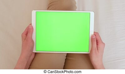 Woman with a tablet PC in hands with a green screen, chroma ...