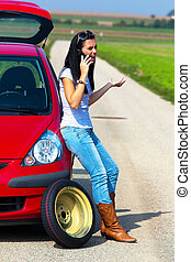 Woman with a tire in a car breakdown