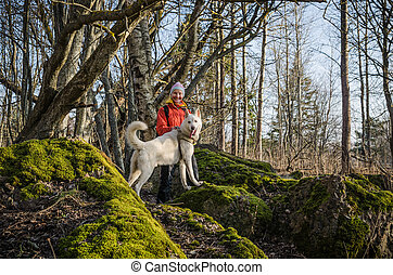 Woman with a white dog in the woods