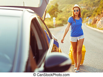 Woman with a yellow suitcase goes to a car parked on the roadside