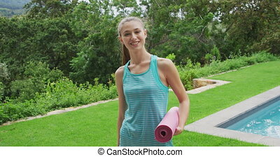 Woman with a yoga mat - Portrait of a young Caucasian woman ...