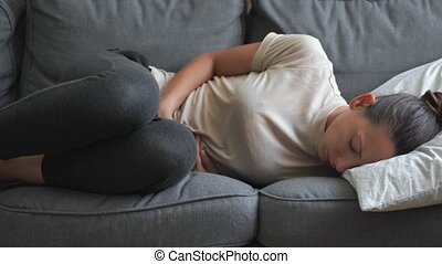 Woman with abdomen pain laying on the grey sofa. Painful periods. Digestive system problems.