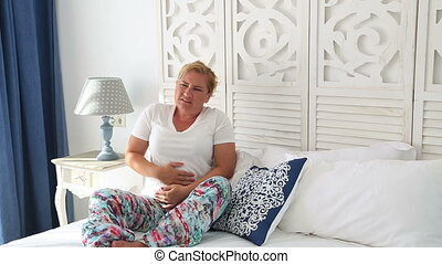 Woman with abdominal pain laying on a bed