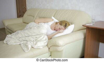 woman with abdominal pain lying on the sofa. Girl drinking pills painkiller