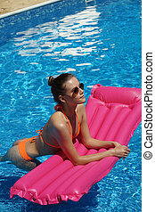 Woman with air mattress in swimming pool