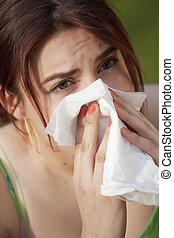 young woman with pollen allergy sneezing in handkerchief