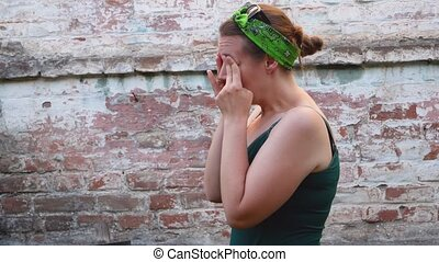 Woman with allergy symptom scratching red eyes on brick background. Sick stressed young girl massaging face nose bridge, infected eyesight problem. Allergic reaction. Conjunctivitis irritated eyes.
