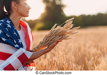 Woman with American flag and with a sheaf of ears in wheat field at sunset. 4th of July. Independence Day patriotic holiday.