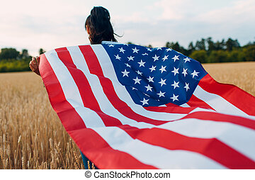 Woman with American flag in field at sunset. 4th of July. Independence Day patriotic holiday.