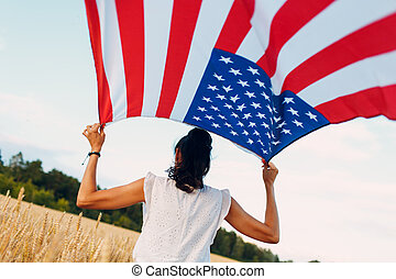 Woman with American flag in wheat field at sunset. 4th of July. Independence Day patriotic holiday.