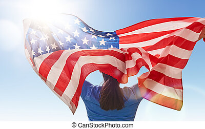 woman with American flag - Patriotic holiday. Happy young...