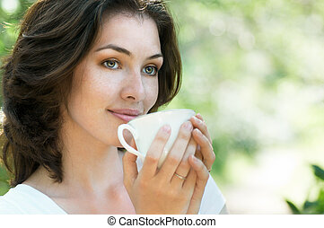Woman with an aromatic coffee in hand