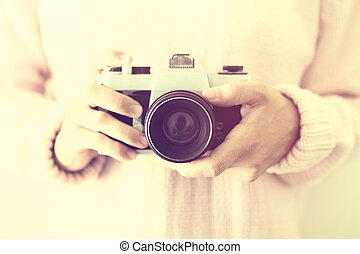 Woman with an old photo camera in hands