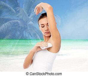 woman with antiperspirant deodorant over beach