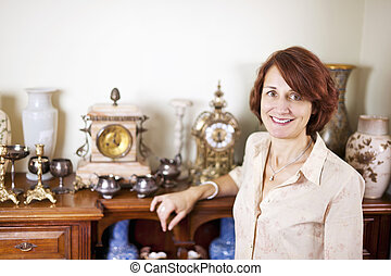 Woman with antique collection - Happy proud woman standing...