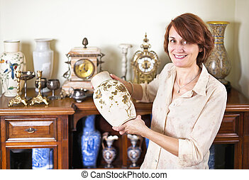 Woman with antique collection - Proud woman holding vase...