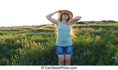 Woman with arms outstretched in a field - Woman with arms...