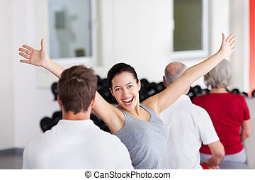 Woman With Arms Raised Sitting With Group In Gym